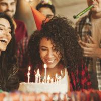 Ein Mädchen, das bereit ist, Kerzen auf einem Geburtstagskuchen auszublasen, umgeben von Freunden