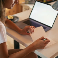 Frau schreibt Geburtstagskarte
