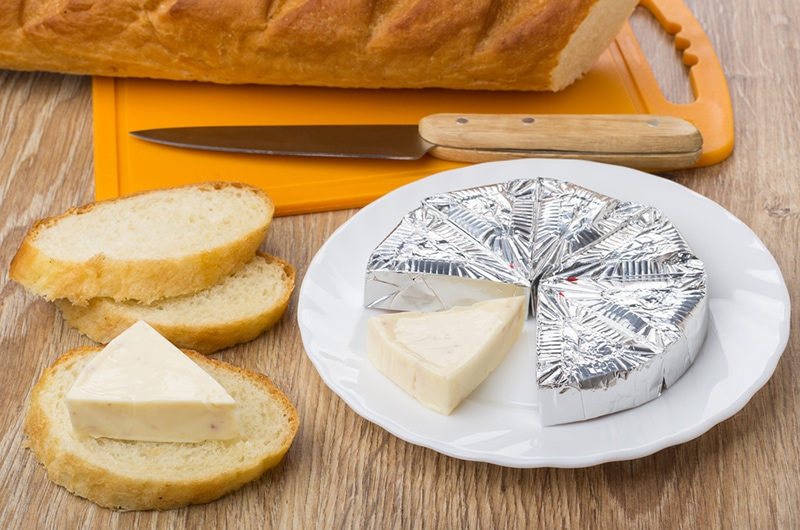 Geschmolzener Käse in Folie auf Teller