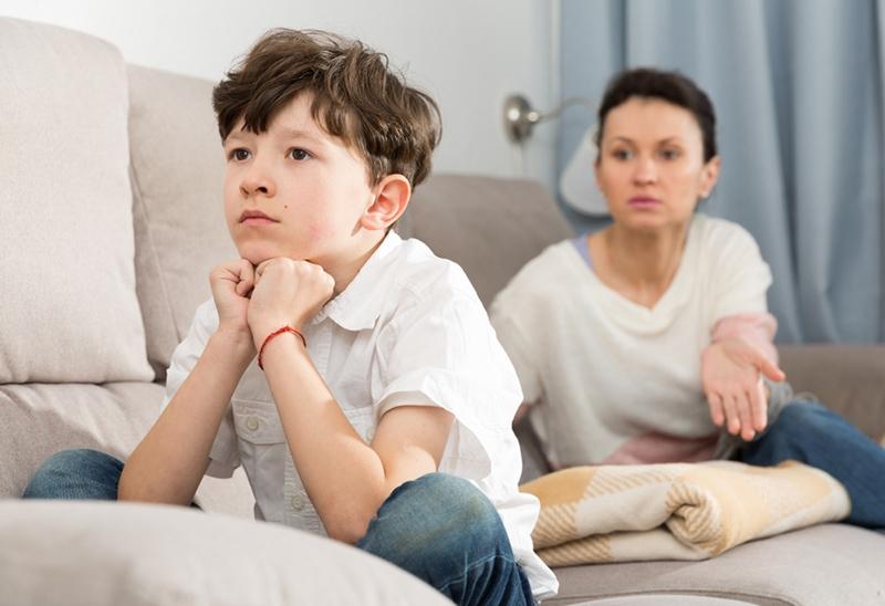 Junge hört zu, wie seine Mutter zu Hause auf der Couch sitzt