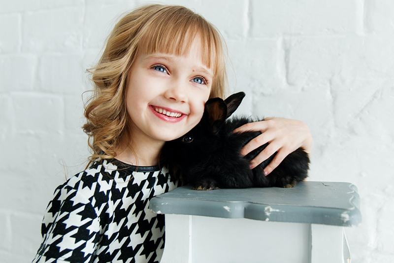 Mädchen hält Kaninchen zurück und lächelt