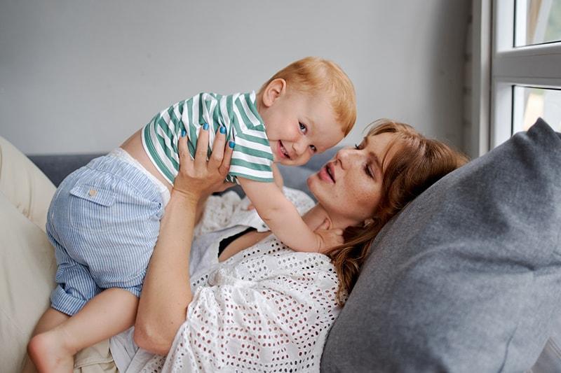 Mutter, die ihren fröhlichen kleinen Sohn hält, während sie auf der Couch liegt