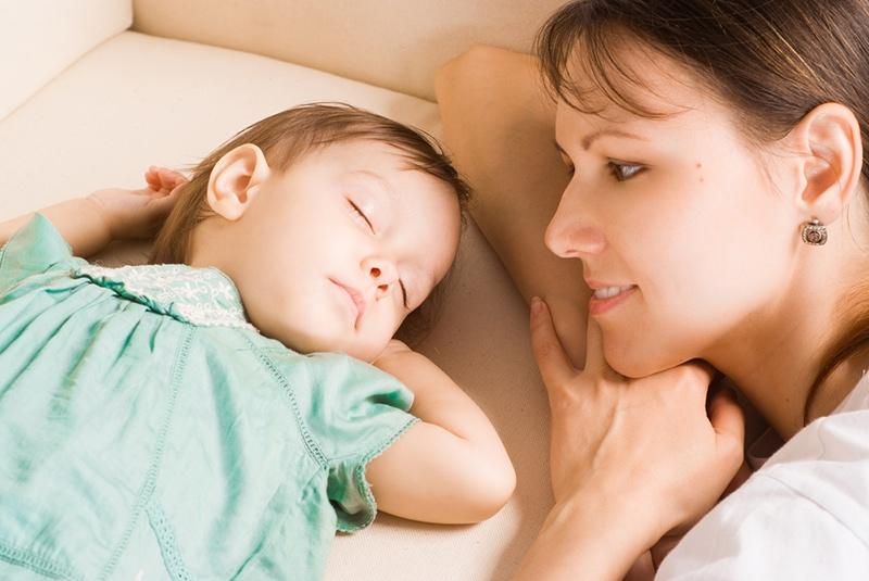 Mutter schaut ihre schlafende kleine Tochter auf dem Sofa an
