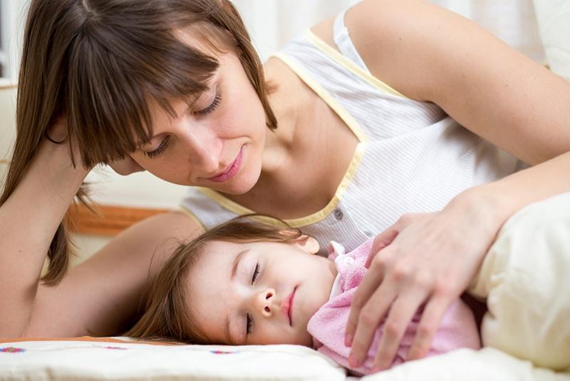 Mutter schaut schlafendes Kind an und umarmt es