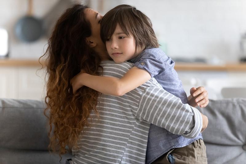 Mutter umarmt Sohn im Wohnzimmer