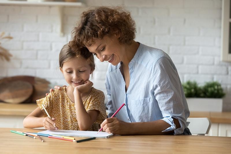 Mutter und Tochter schreiben auf Papier auf den Tisch
