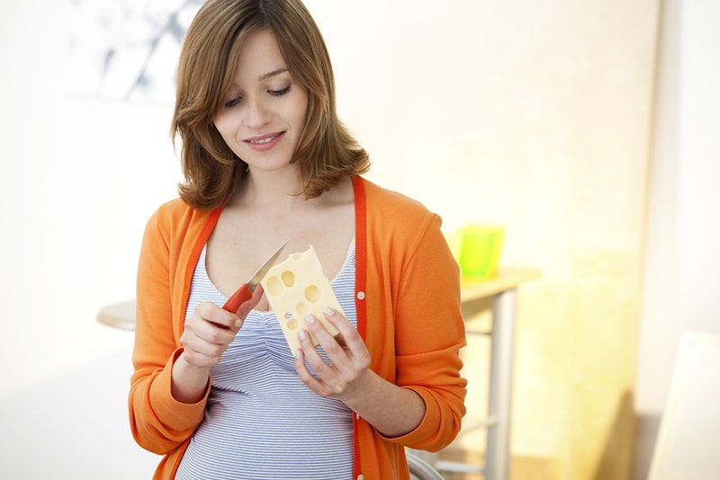 Schwangere schneidet Käse in der Küche