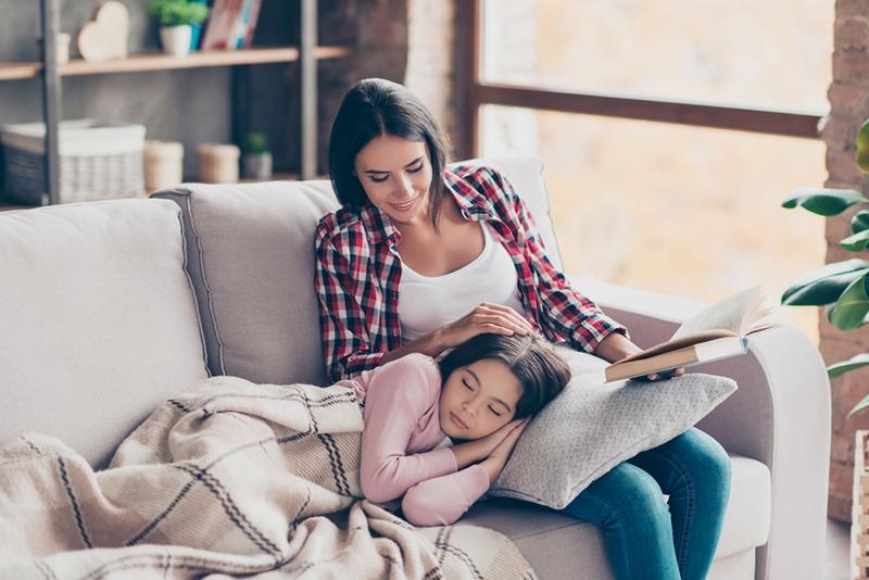 Süßes kleines Mädchen ist auf einer Couch eingeschlafen, während ihre Mutter ein Märchen las