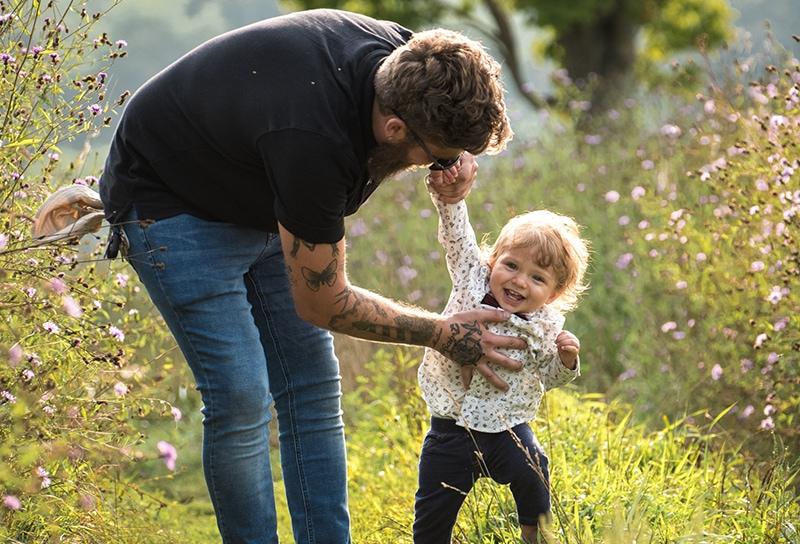 Vater hält lächelndes Baby für die Hand auf der Wiese