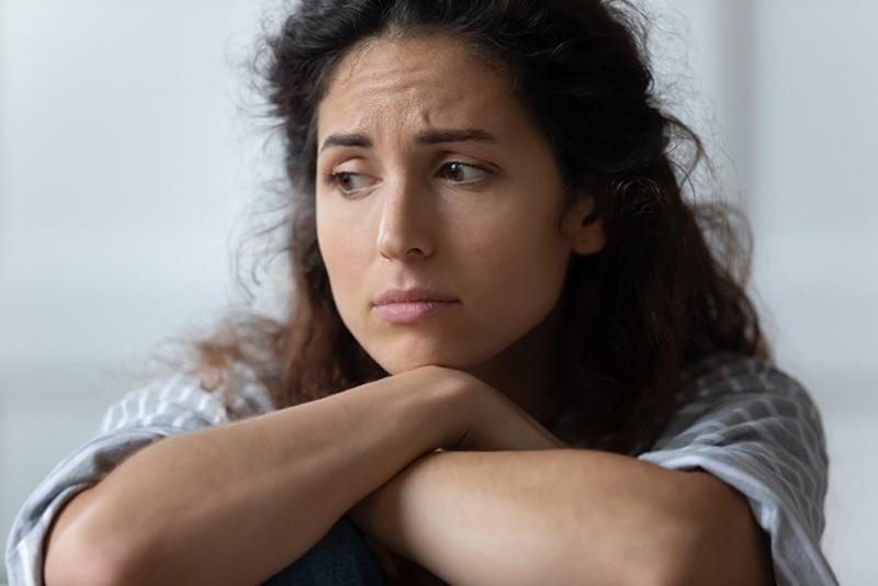 besorgte Frau, die beiseite schaut und über ein Problem nachdenkt