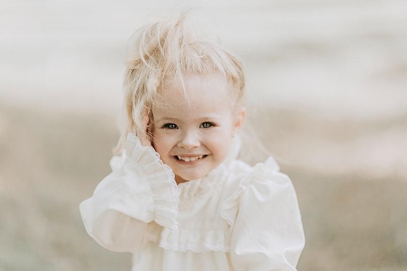 blondes kleines Mädchen, das mit weißer Bluse lächelt