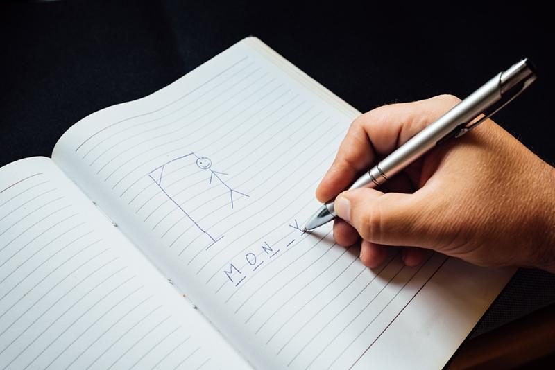 eine Person, die ein traditionelles Spiel des Henkers auf Papier spielt