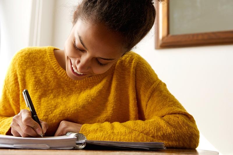 fröhliche Frau schreibt in ein Notizbuch am Tisch