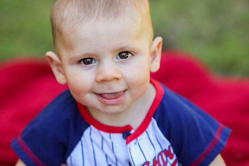 kleiner Junge lachelt auf roter Matte sitzend