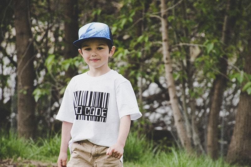 kleiner Junge mit Mütze im Park stehen