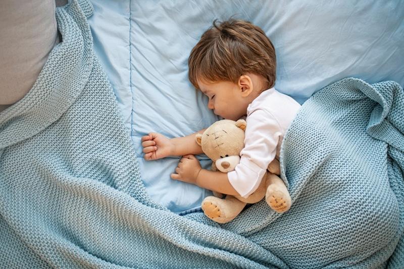kleiner Junge schläft zusammen mit Teddybär