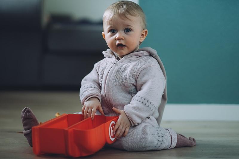 Baby, das auf dem Boden sitzt und ein Spielzeug hält