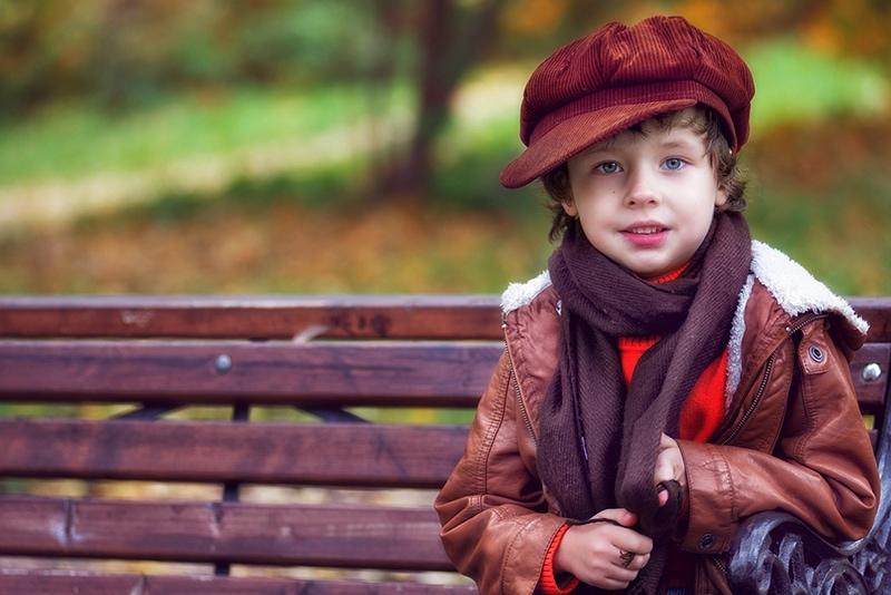 kleiner Junge sitzt auf der Bank im Park