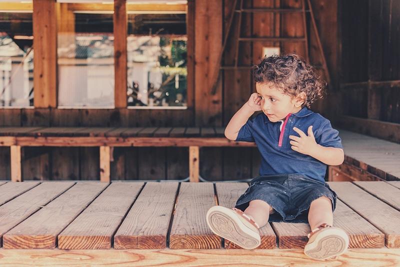 kleiner Junge sitzt auf der Holztheke und schaut beiseite