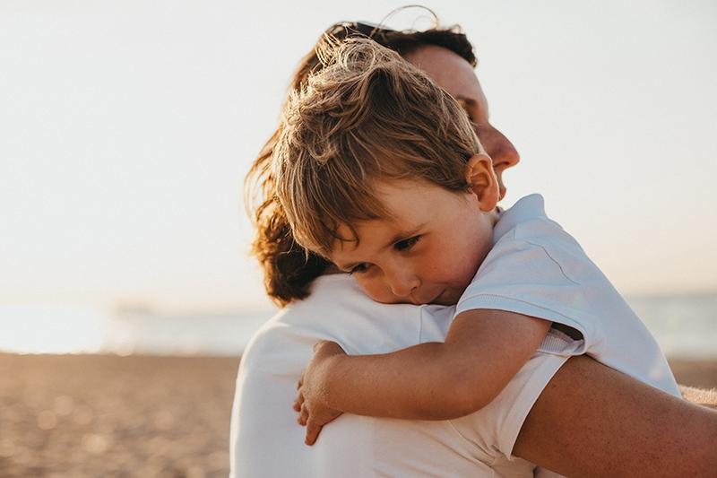 kleiner Junge umarmt seine Mutter am Strand