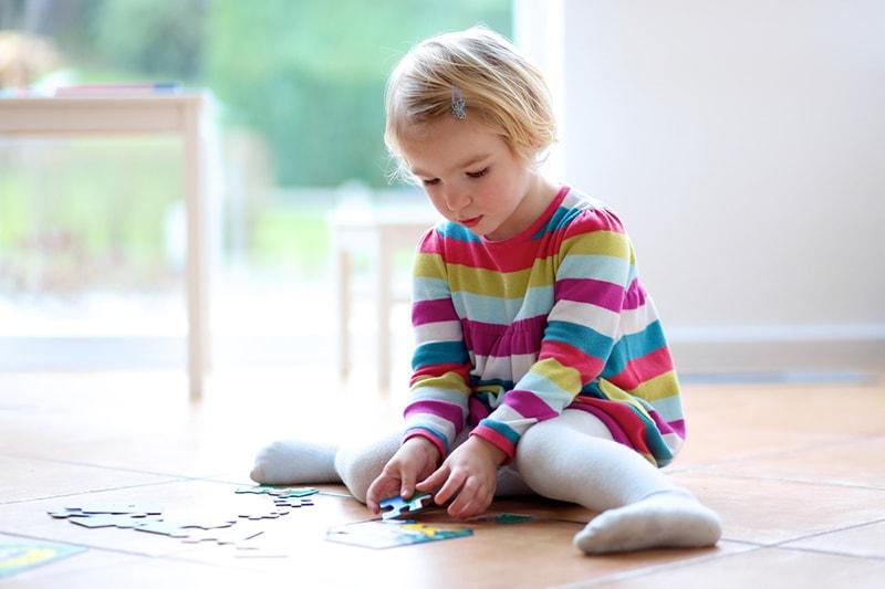 kleines Mädchen spielt mit Puzzles, die zu Hause auf den Fliesen sitzen
