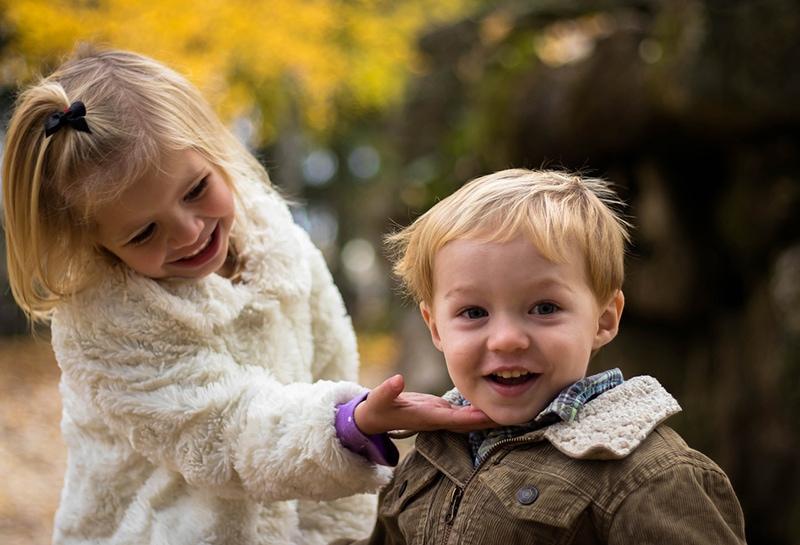 kleines Mädchen, das einen kleinen lächelnden Jungen kuschelt, während es im Park steht