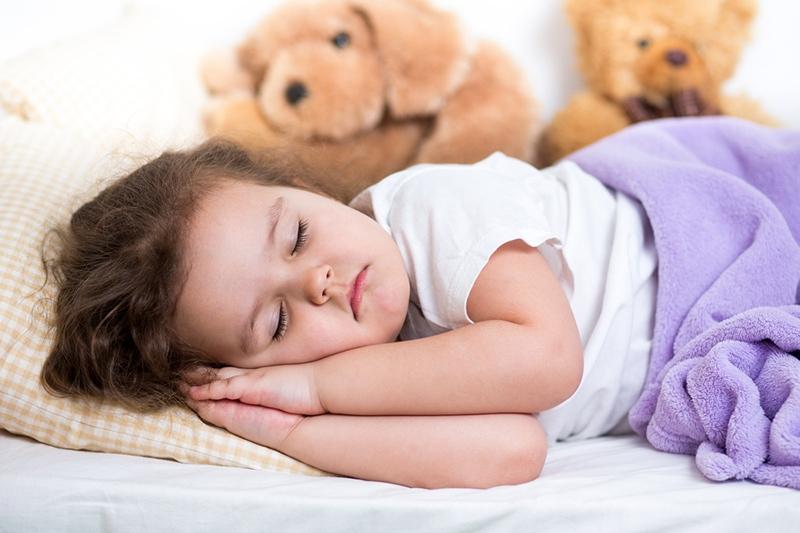 kleines Mädchen macht ein Nickerchen im Bett