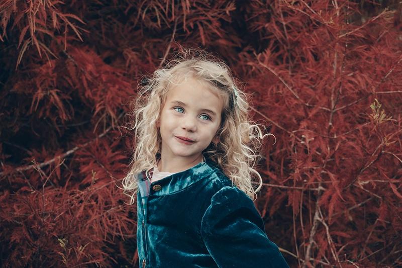 kleines Mädchen mit blauen Augen, das in der Nähe des Baumes steht