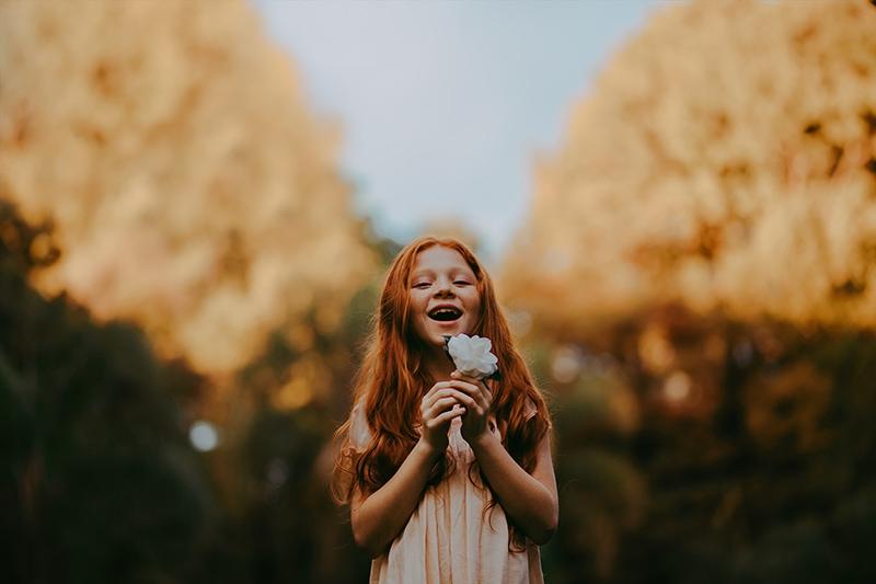 kleines rothaariges Mädchen, das weiße Blume lächelt und hält