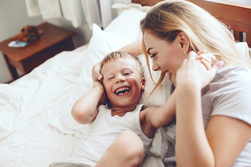 lächelnde Mutter und ihr lächelnder Sohn spielen im Bett