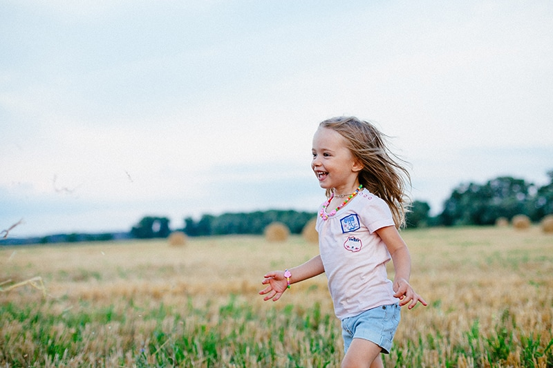 lächelndes kleines Mädchen, das auf der Wiese läuft
