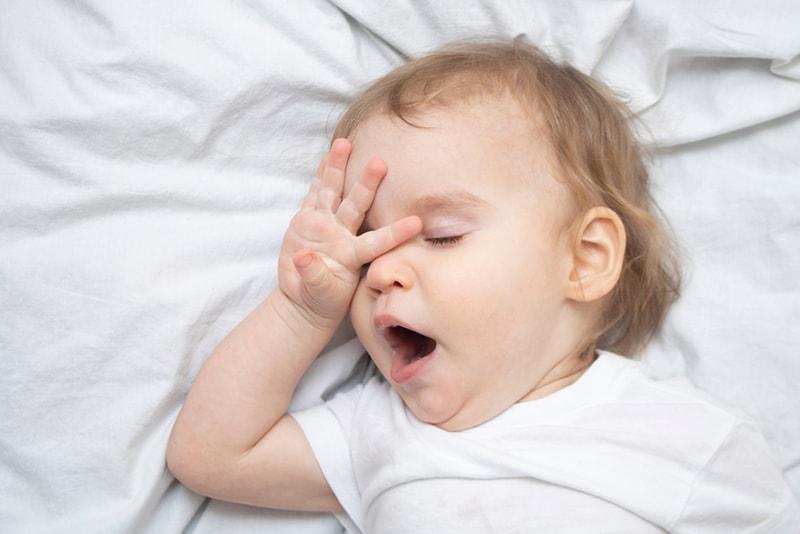 schläfriges Baby reibt sich die Augen und gähnt