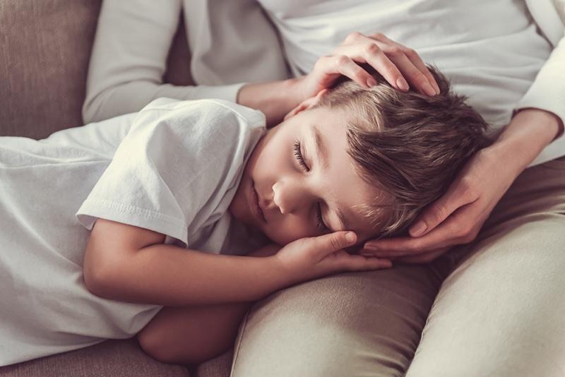 süßer kleiner Junge, der auf dem Schoß der Mutter ein Nickerchen macht