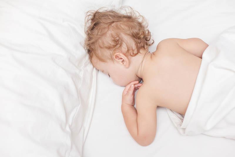 süßes Baby mit lockigem Haar, das auf Bauch im Bett schläft