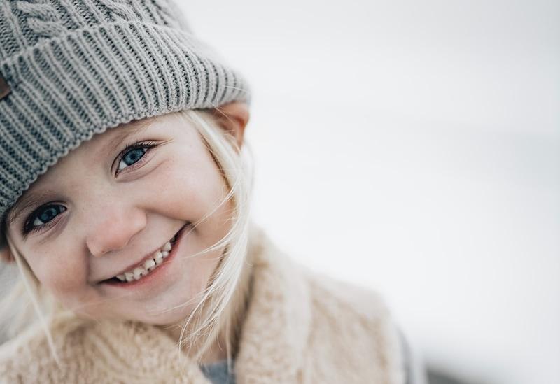 süßes blondes kleines Mädchen mit grauer Mütze