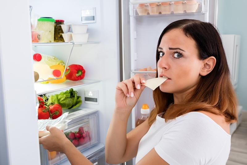 verwirrte Frau isst Käsescheibe vor offenem Kühlschrank