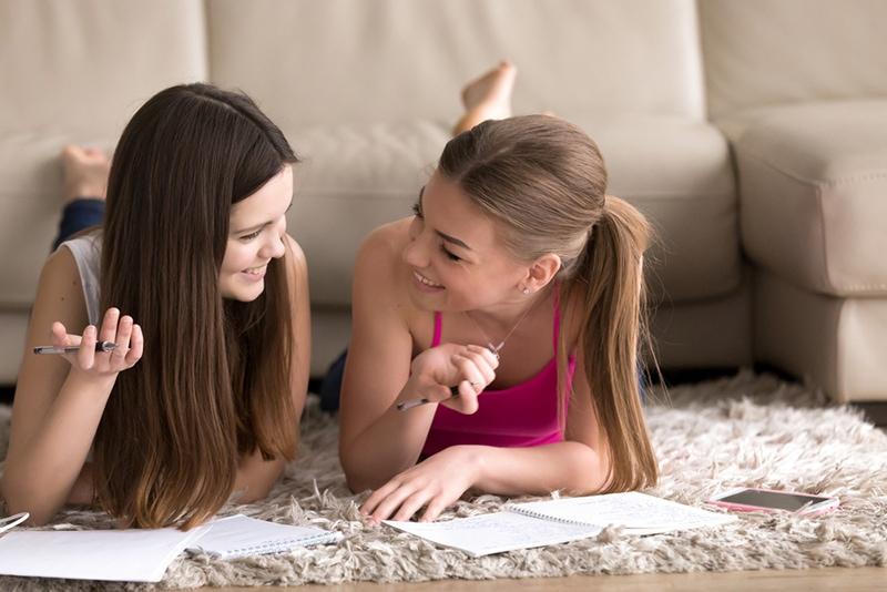 Zwei fröhliche Mädchen schreiben in Notizblock und liegen auf Teppich